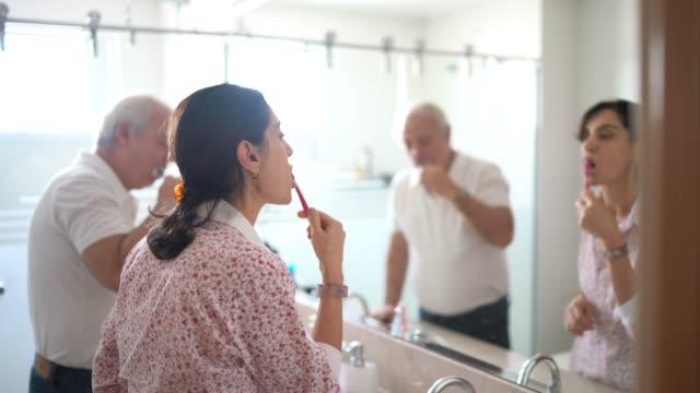 vídeos de stock, filmes e b-roll de casal de idosos escovando os dentes no banheiro - américa do sul