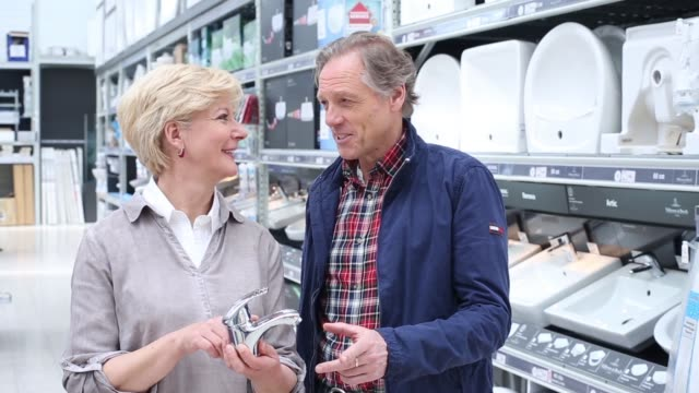 Senior couple buying a water-tap