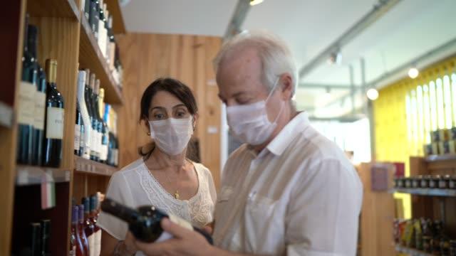 vídeos y material grabado en eventos de stock de pareja senior comprando vino con mascarilla en la tienda - mercado espacio de comercio