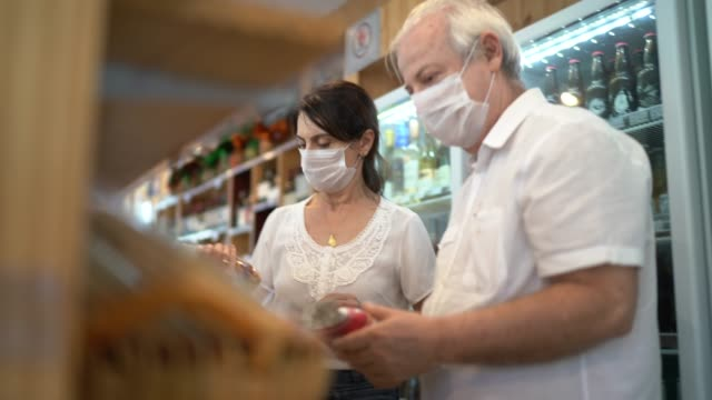 senior couple buying with face mask at store - price stock videos & royalty-free footage