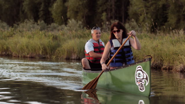 senior couple canoeing on a calm river - idaho stock videos & royalty-free footage