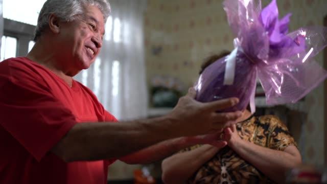 vídeos de stock, filmes e b-roll de casal sênior, comemorando a páscoa brasileira com ovos de chocolate - alegria