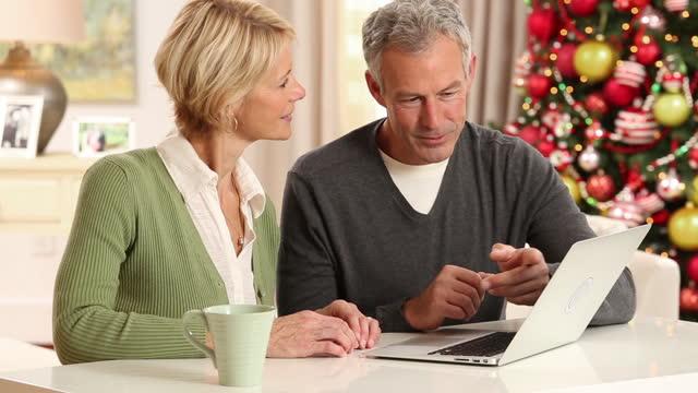 senior couple christmas shopping on line