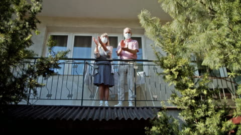 senior couple clapping from balcony during covid-19 quarantine - clapping hands stock videos & royalty-free footage