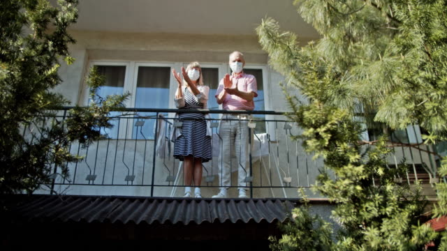 senior couple clapping from balcony during covid-19 quarantine - balcony stock videos & royalty-free footage
