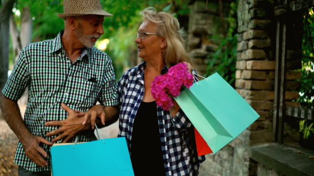 senior couple coming back from shopping. - sun hat stock videos & royalty-free footage