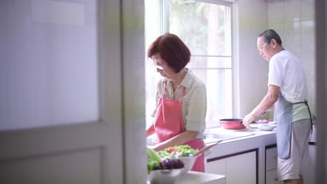 キッチンで料理をする先輩カップル - 台所点の映像素材/bロール