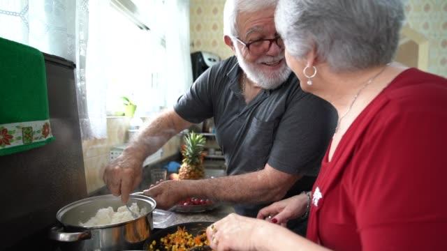 vídeos de stock, filmes e b-roll de casal sênior cozinhar juntos - cozinha