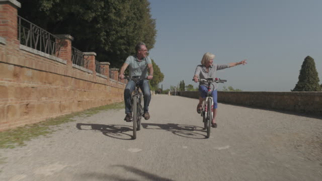 senior couple cycling on electric bicycles - wolkenloser himmel stock-videos und b-roll-filmmaterial
