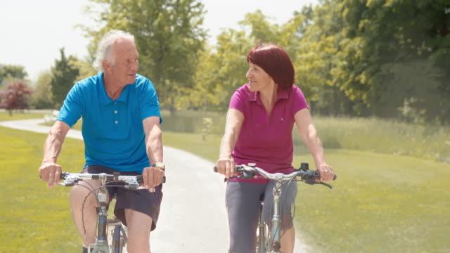 SLO MO Senior couple cycling through the park