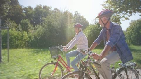 stockvideo's en b-roll-footage met senior paar ts fietsen door het zonnige park - cycling