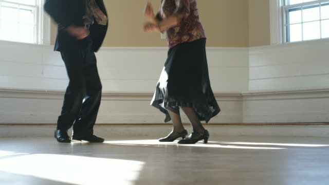 MS, Senior couple dancing and falling on floor in empty room, Hingham, Massachusetts, USA