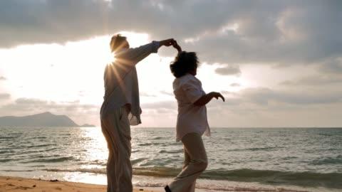 vídeos y material grabado en eventos de stock de senior pareja bailando en la playa en día soleado, senior pareja relajante junto al mar. altos días de fiesta, vacaciones - viejo