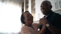 Senior couple dancing at kitchen