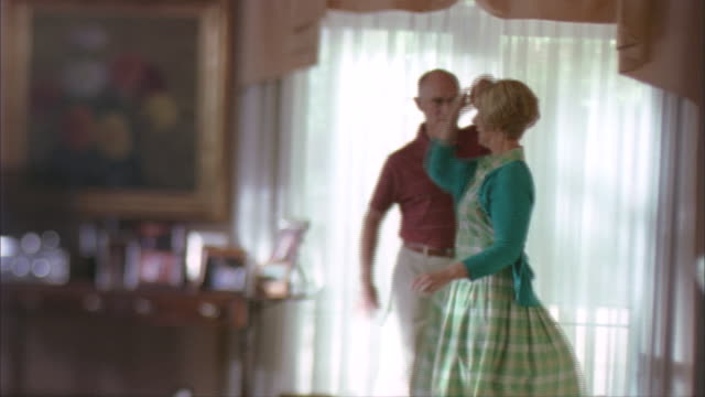 SLO MO, WS, DEFOCUS, Senior couple dancing in living room, Rockford, Illinois, USA