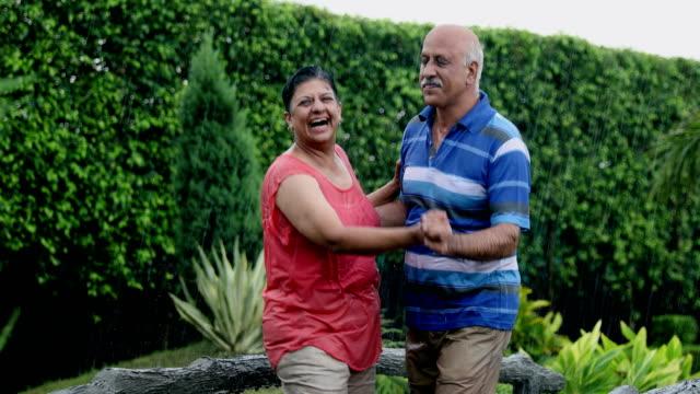 senior couple dancing in the rain season, delhi, india - 50 54 years stock videos & royalty-free footage