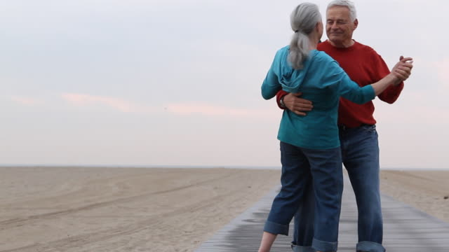WS PAN Senior couple dancing on beach boardwalk / Los Angeles, California, USA