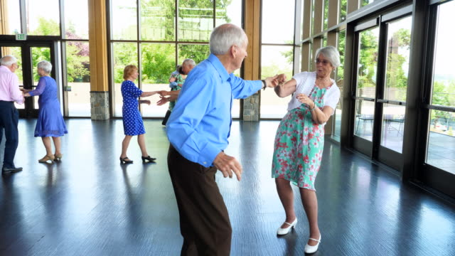 ms senior couple dancing together with friends in community center - 70 79 jahre stock-videos und b-roll-filmmaterial