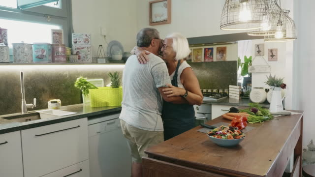 Senior Couple Dancing while Preparing Lunch in Family Kitchen