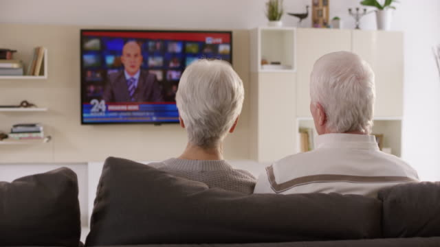 ds senior couple discussing news they are watching on tv - guardare la tv video stock e b–roll