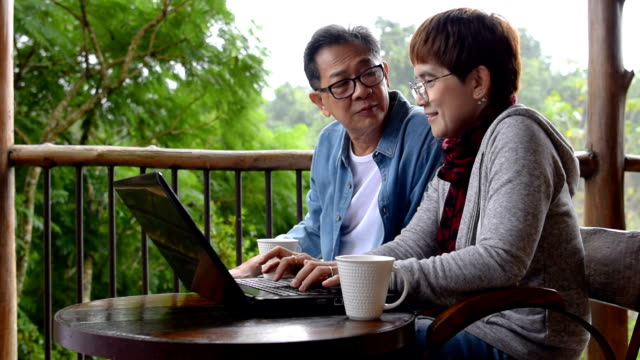 Senior couple discussing while using laptop on the balcony