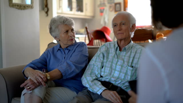 Senior couple discussing with female caregiver