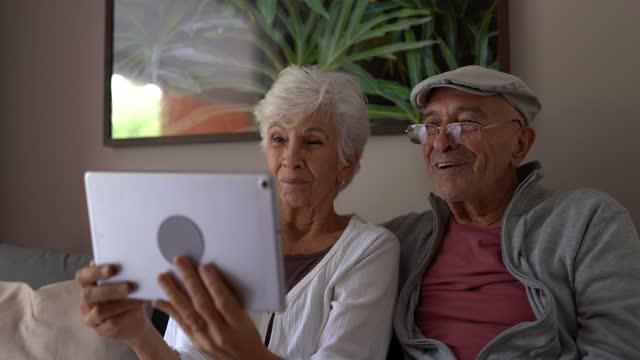 stockvideo's en b-roll-footage met hoger paar dat een videogesprek op digitale tablet thuis doet - looking at camera