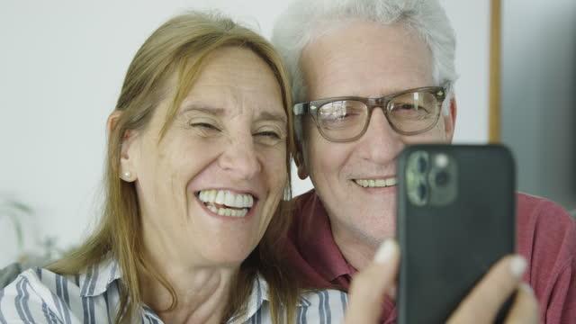 vídeos de stock, filmes e b-roll de casal sênior fazendo uma chamada de vídeo com smarthphone de casa - imagem em movimento