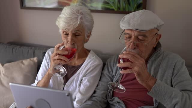vídeos de stock, filmes e b-roll de casal de idosos fazendo um happy hour virtual em tablet digital em casa - jovem de espírito