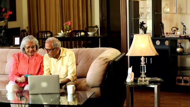 Senior couple doing online shopping on laptop, Delhi, India
