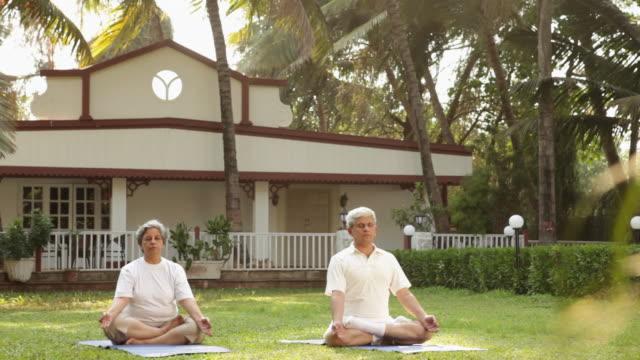 Senior couple doing padmasana in a lawn