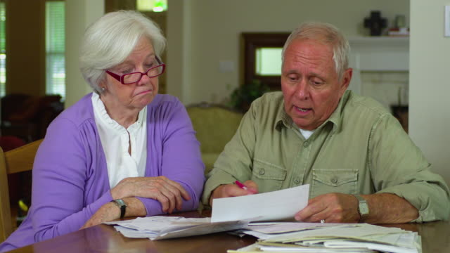 ms senior couple doing paperwork in living room, austin, texas, usa - 60 69 years stock videos & royalty-free footage