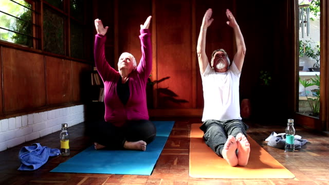 senior couple doing yoga prayer pose - prayer pose yoga stock videos & royalty-free footage