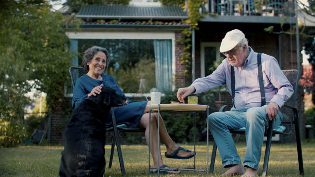 senior couple drinking coffee in garden of their house with dog - outdoors stock videos & royalty-free footage