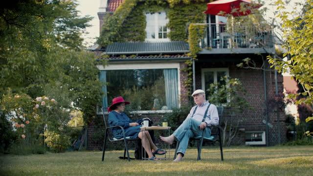 stockvideo's en b-roll-footage met senior couple drinking coffee in garden of their house with dog - huisdiereigenaar