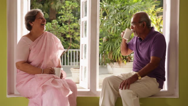 senior couple drinking tea at window sill - indian couple tea stock videos & royalty-free footage