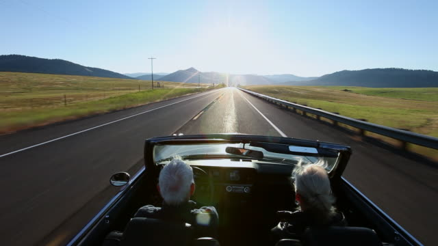 vídeos de stock, filmes e b-roll de ws senior couple driving convertible car at sunrise on rural road/washington, usa - exultação