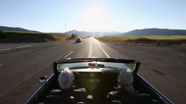 ws senior couple driving convertible car at sunrise on rural road/washington, usa - auto convertibile video stock e b–roll