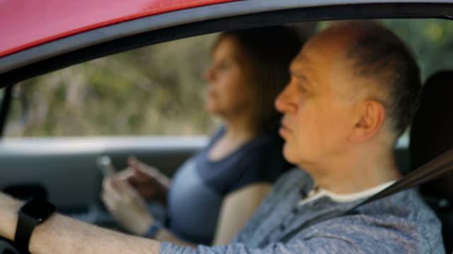 車の中で運転し、ナビゲーションとして携帯電話を使用してシニアカップル - 中年点の映像素材/bロール