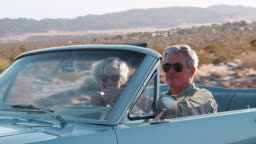 Senior couple driving in open top car on a desert highway