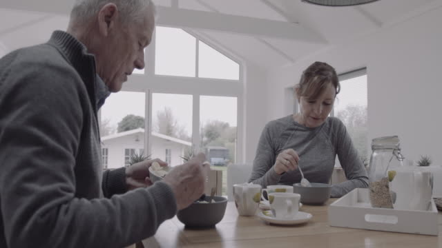senior couple eating healthy breakfast at kitchen table together at home, day in life - seniorenpaar stock-videos und b-roll-filmmaterial
