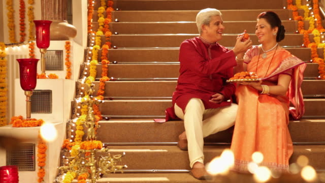 Senior couple eating sweets in diwali festival