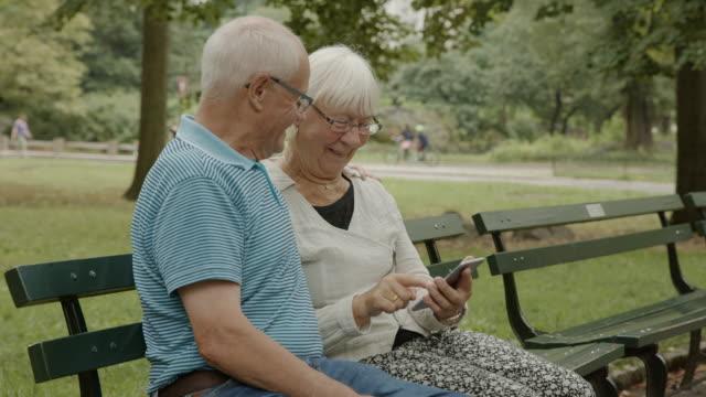 Senior couple elder smartphone social media New York surfing net