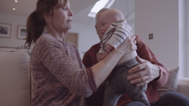 senior couple embracing grandchild on sofa at home, multi generation togetherness - sollevare video stock e b–roll