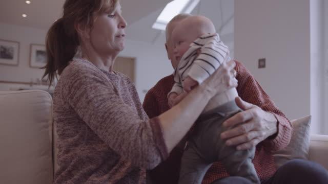 senior couple embracing grandchild on sofa at home, multi generation togetherness - nonno video stock e b–roll