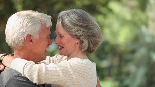 cu pan senior couple embracing outdoors / richmond, virginia, usa - grey hair stock videos and b-roll footage