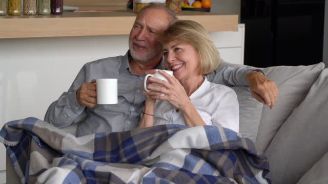 vídeos de stock e filmes b-roll de senior couple enjoying a coffee cuddling together on couch while watching tv talking and smiling - adulto maduro