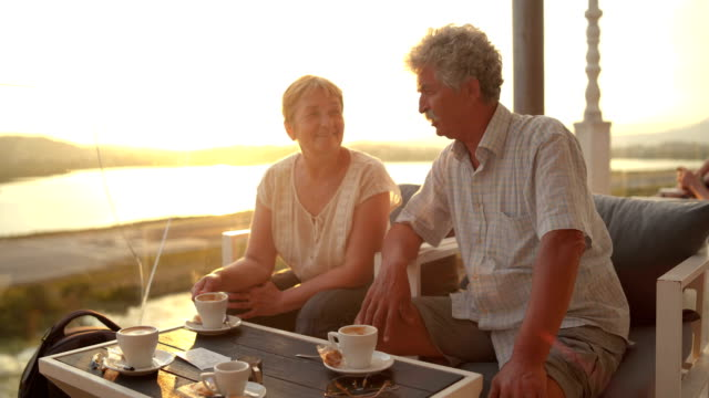 senior couple enjoying coffee at sunset - greece stock videos & royalty-free footage