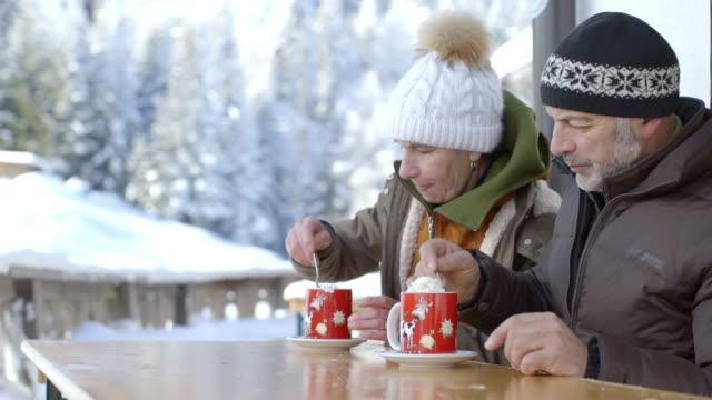 Senior couple enjoying hot chocolate during winter