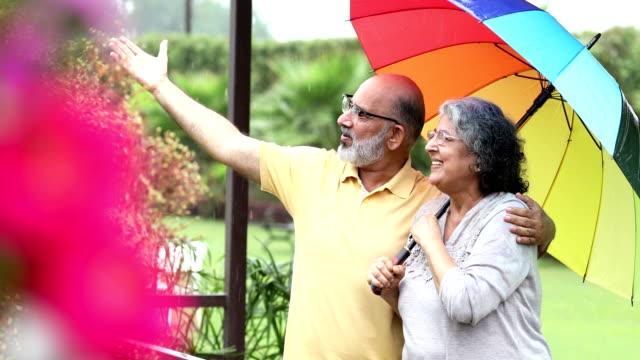 vidéos et rushes de senior couple enjoying in rain season, delhi, india - fondu d'ouverture